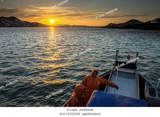 The sun sets over Kulukak Bay in the Bristol Bay region as a commercial fishing crew takes a break, Southwest Alaska, USA