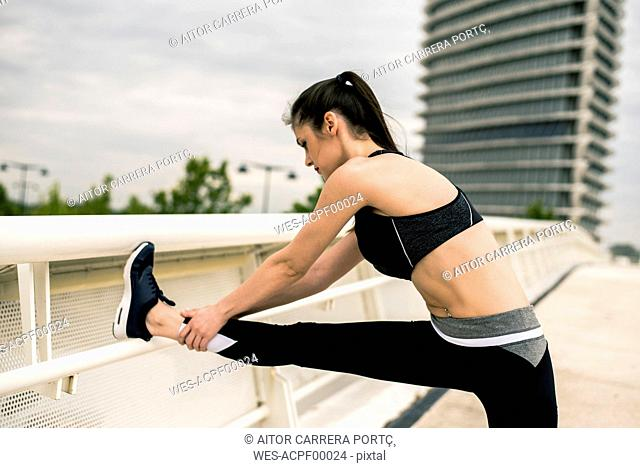 Sportive woman stretching leg