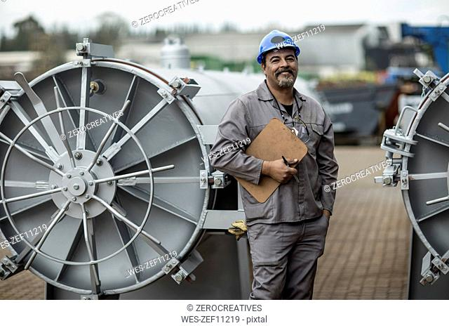 Worker in factory checking horizontal retorts