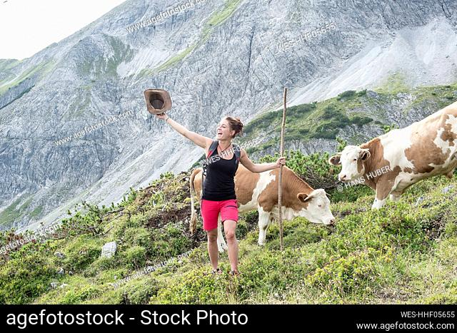 Cheerful woman on mountain while cows grazing in background