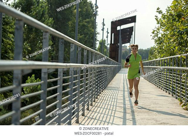 Young woman running on bridge