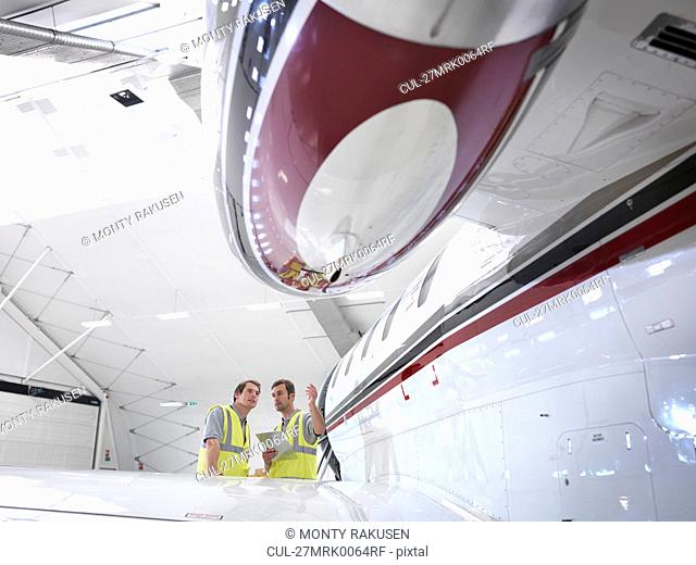 Engineers inspecting jet aircraft