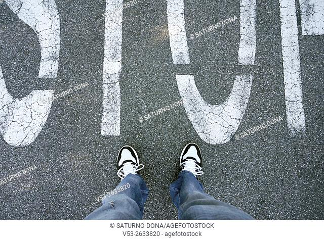 Male feet standing on asphalt with stop sign marking
