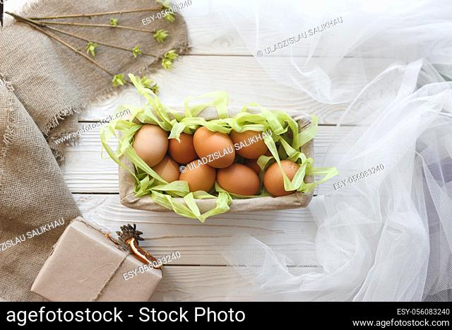 Basket with eggs and spring decor on a white wooden background