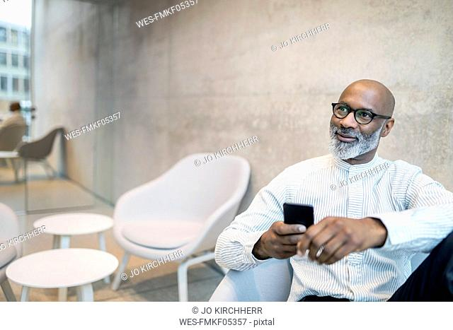 Portrait of smiling mature businessman with smartphone