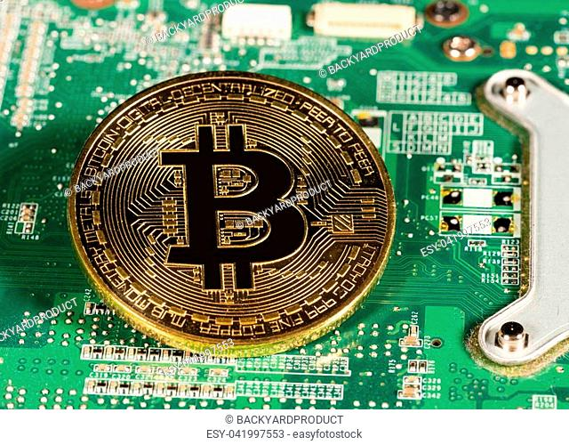 Bitcoin coin on a computer board to illustrate blockchain and cyber currency