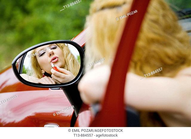 Applying make-up in car's outside mirror
