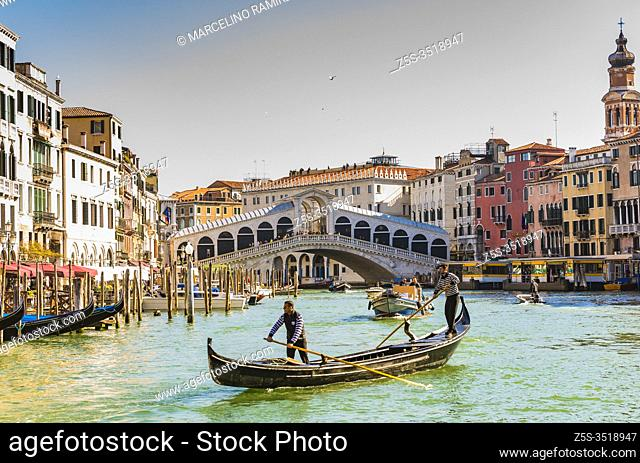 Gondolier guides tourists mounted on gondola near the Rialto bridge. Grand Canal. Venice, Veneto, Italy, Europe