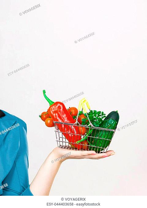 Lose weight, buying healthy food, vegetarian products. Woman hand holding little shopping basket with high fibre red green vegetables inside, on grey