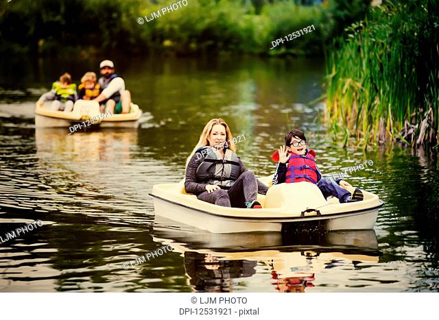 A mother and father take their three sons paddle boating on a lake in a city park; Edmonton, Alberta, Canada
