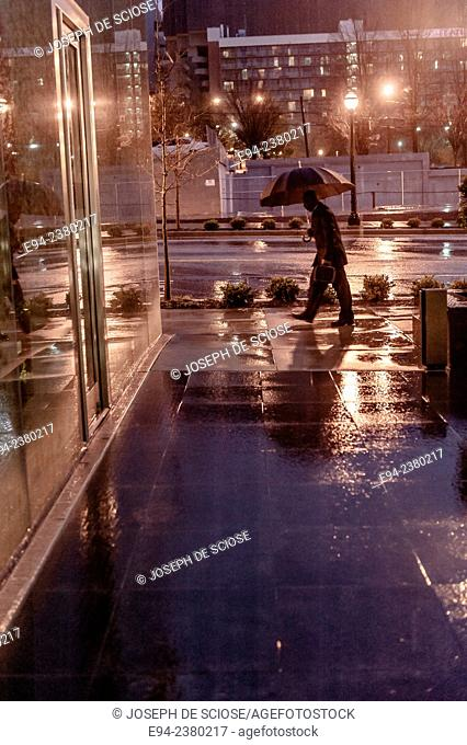 A partial view of a man carrying an umbrella on a city sidewalk on a rainy morning