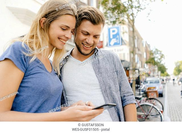 Netherlands, Maastricht, happy young couple looking at cell phone the city