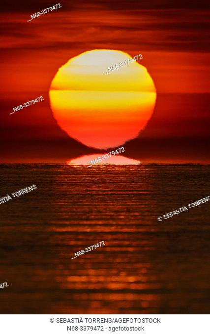 Sunrise and reflections on the sea at Pollença Bay, Majorca, Spain