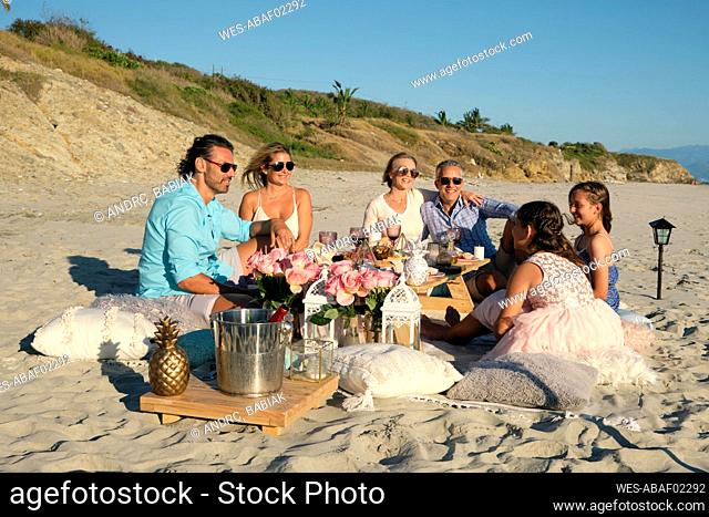 Family and friends enjoying picnic while sitting at beach against blue sky during sunset. Riviera Nayarit, Mexico