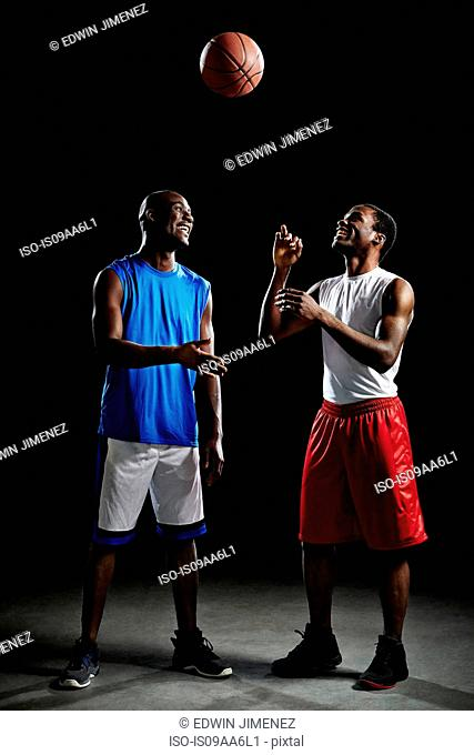 Studio shot of two basketball players with ball mid air