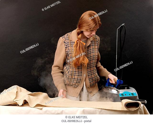 Young female designer steam ironing fabric