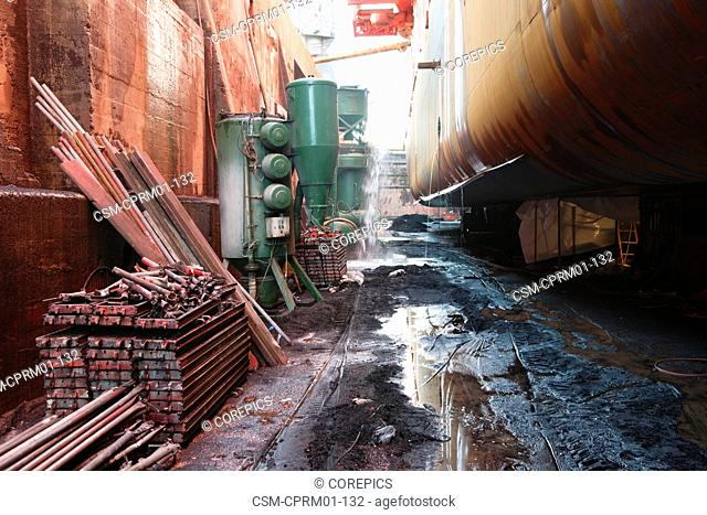 Various heavy equipment at an industrial dry dock, seen from the bottom of the dock, with ship's hull on the right