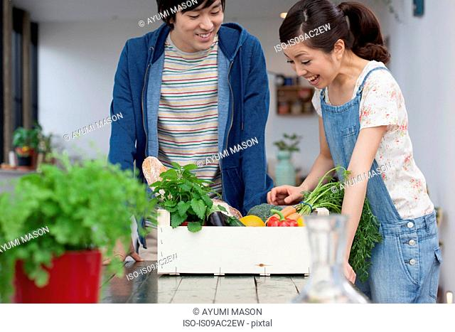 Young couple in kitchen with box of vegetables