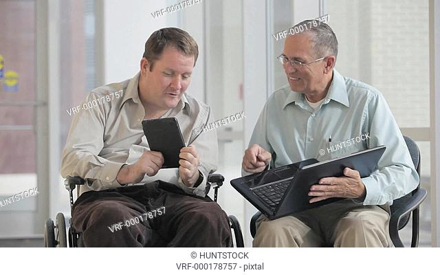 Two men comparing a tablet and a computer, one man quadriplegic in a wheelchair