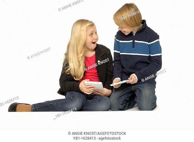 Ten year old girl and eleven year old boy using tablet computers and smiling