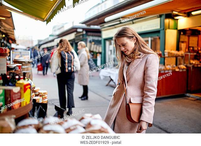 Austria, Vienna, woman looking at offer at Naschmarkt