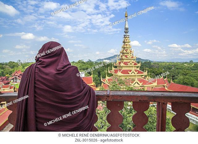 Monk overlooking Mandalay Royal Palace in Mandalay, Myanmar
