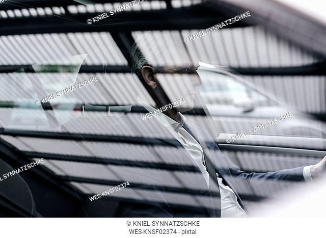 Businessman behind car window