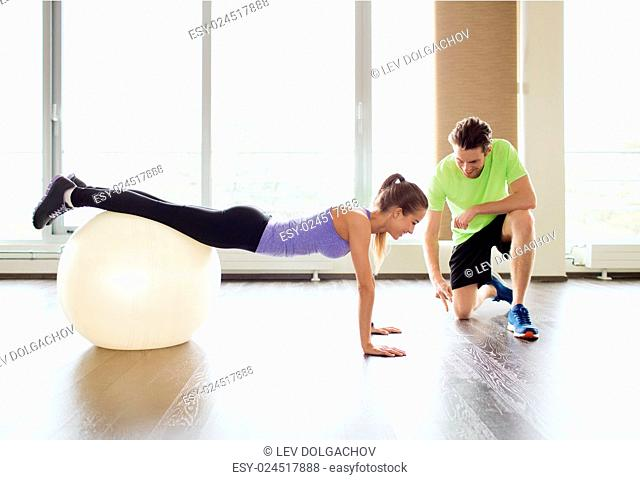 sport, fitness, lifestyle and people concept - smiling man and woman working out with exercise ball in gym