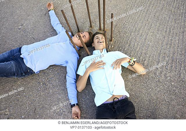 Two young men lying on floor, exhausted