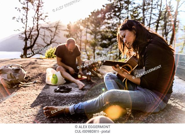 Man and woman relaxing, cooking food and playing guitar on The Malamute, Squamish, Canada