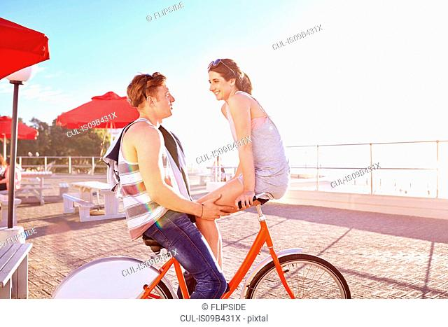 Couple on promenade on bicycles face to face smiling