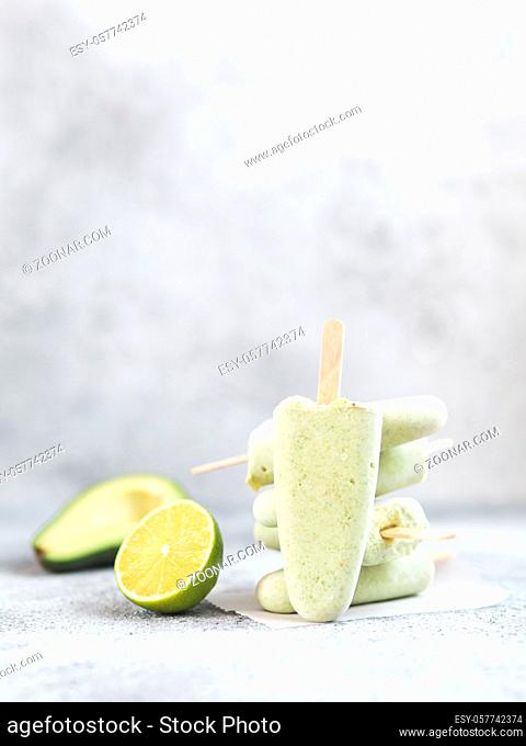 Homemade raw vegan avocado lime popsicle. Sugar-free, non-dairy green ice cream on gray cement textured background. Copy space