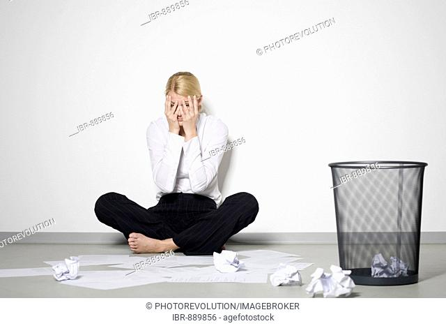 Young blonde woman sitting by the wall in despair amongst crumpled paper