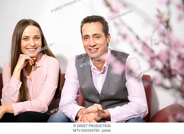 Young couple sitting on sofa waiting smiling