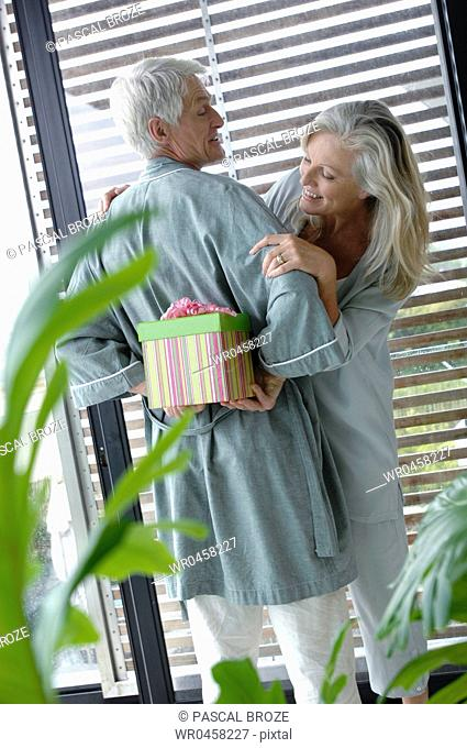 Rear view of a mature man hiding a gift behind his back with a mature woman peeking