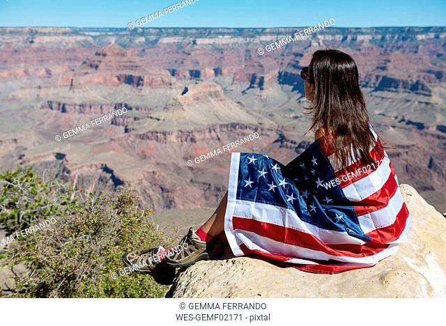 USA, Arizona, woman wrapped in American flag enjoying view of Grand Canyon National Park