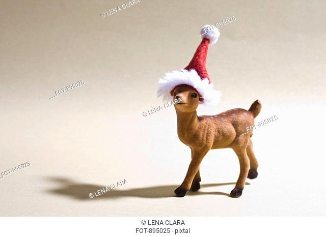 A reindeer figurine wearing a Santa hat