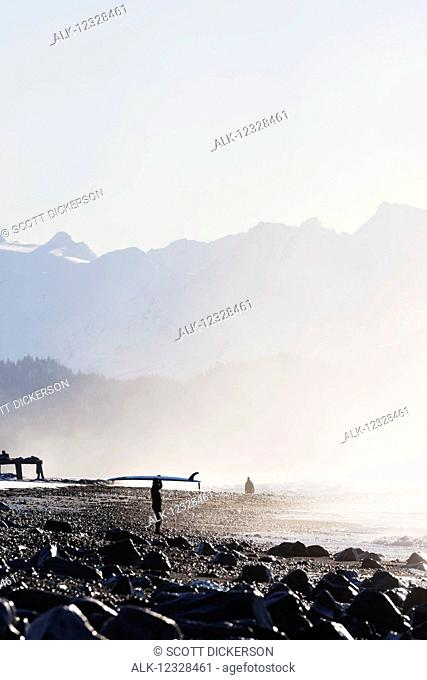 Female surfer standing along the wet shore of Kachemak Bay with her surfboard over her head, South-central Alaska; Homer, Alaska, United States of America