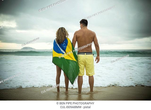 Young couple, woman wrapped in brazilian flag, Ipanema Beach, Rio de Janeiro, Brazil