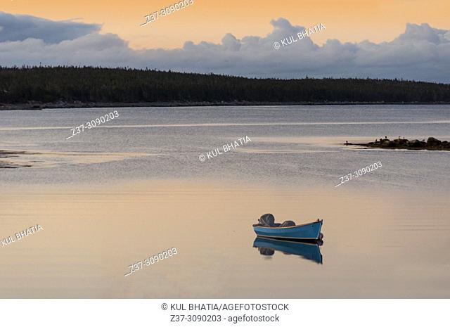 A blue boat floats in the tranquil waters of a cove in the Atlantic ocean, Halifax, Nova Scotia, Canada, early in the morning