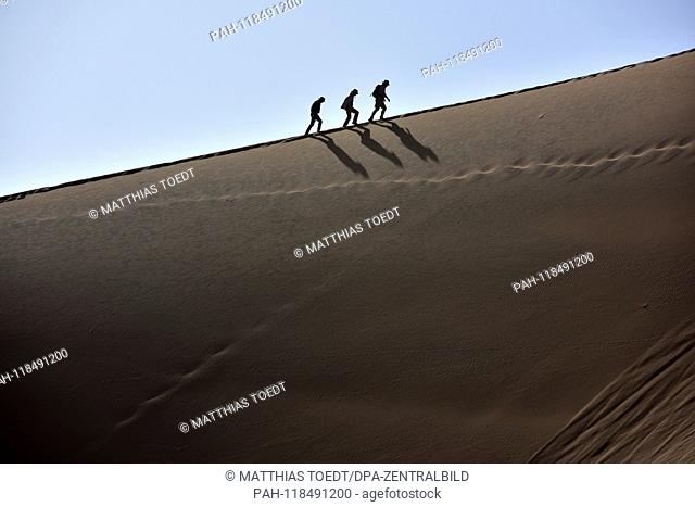 These three visitors do their best to climb the dunes surrounding the Dead Vlei, which are among the highest in the world, taken on 01.03.2019