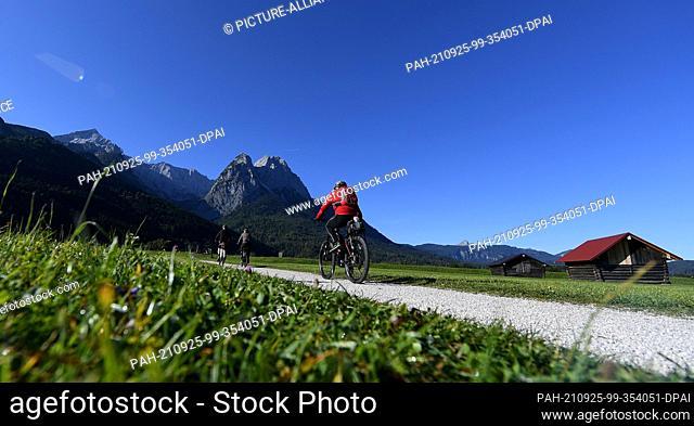 25 September 2021, Bavaria, Garmisch-Partenkirchen: Cyclists take advantage of the beautiful autumn weather for an excursion