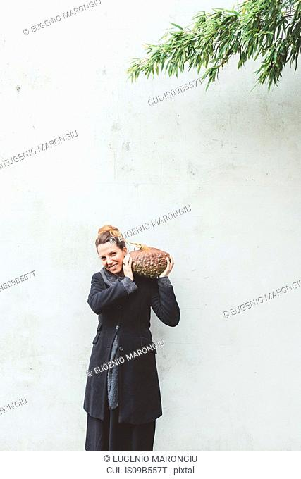 Portrait of young woman carrying pumpkin on shoulder in front of white wall