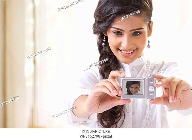 Young woman taking self photo with camera