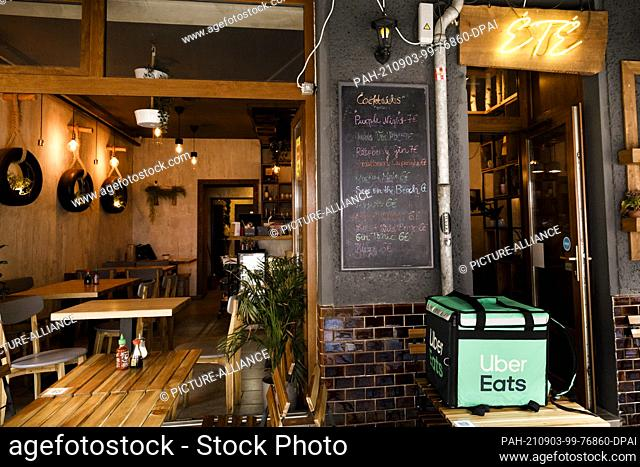 PRODUCTION - 02 September 2021, Berlin: A transport box of the delivery service Uber Eats stands on a table in front of the restaurant ETE in the district...