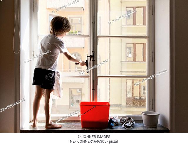 Boy cleaning window