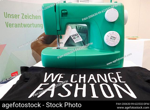 """30 June 2020, Hamburg: ILLUSTRATION - A green sewing machine and a T-shirt with the inscription """"""""We change fashion"""""""" can be seen at a press conference on the..."""