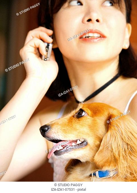 Close-up of a mature woman with a dog and talking on a mobile phone