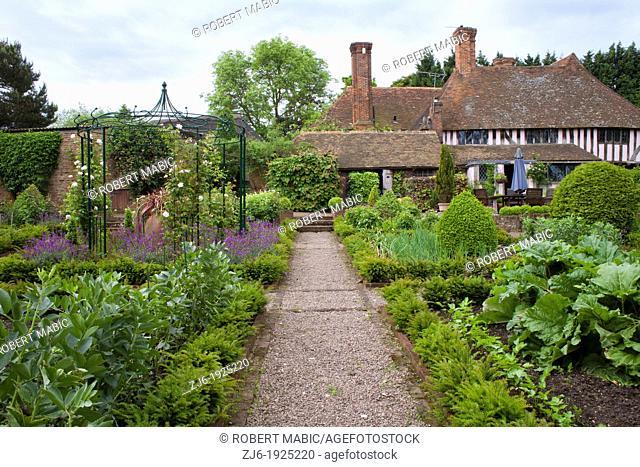 Gravel pathway through kitchen garden borders leading to the house, Bexon Manor Kent England