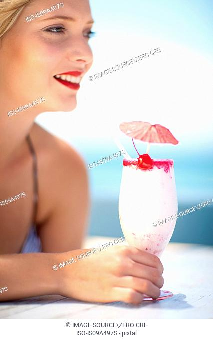 Woman having tropical drink outdoors